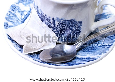Macro shot of a tea bag and spoon on a decorative cup and plate - stock photo