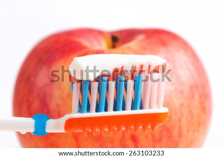 Macro shot of a toothbrush with toothpaste and a blurred red apple in the background - stock photo