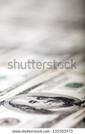 Macro shot of a 100 US$ money note with a very shallow depth of field, focused on the eye of Benjamin Franklin. The bill is located amongst many other identical (but defocused) bills. - stock photo