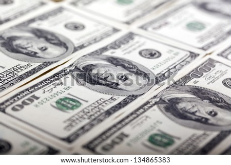 Macro shot of Benjamin Franklin's portrait on a 100 US$ money note, with two more notes above and below it. Shallow depth of field. - stock photo