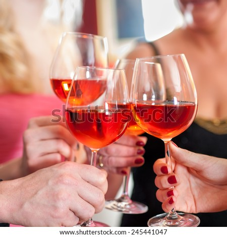 Macro Shot of Hands Raising Glasses of Tasty Red Wine in a Social Gathering. - stock photo