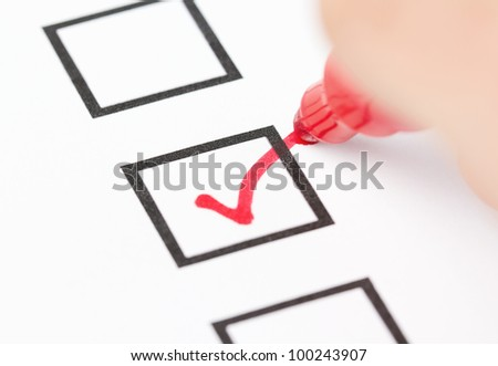 Macro shot of human hand drawing red check mark in the checklist box - stock photo