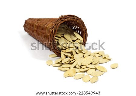 Macro Shot of Roast Pumpkin Seeds in Wicker Basket Isolated on White Background - stock photo