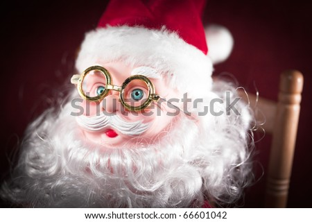 Macro shot of Santa Claus puppet with glasses sitted on a chair - stock photo