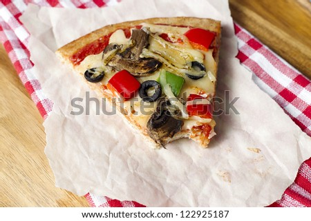 Macro shot of slice of pizza on tissue paper and napkin. - stock photo