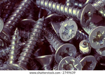Macro shot of small crosspoint screws, with a warm tone - stock photo