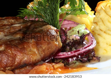 macro steak with potato gratin decorated with greens and onion - stock photo