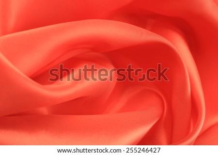 macro texture of satin fabric coral color studio  - stock photo
