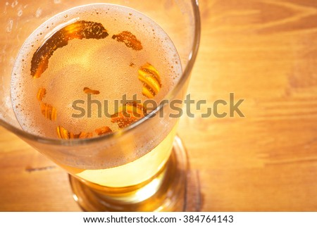 macro view of a beer glass on the table with froth - stock photo