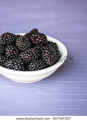 Macro view of a group of juicy blackberries in a white bowl, shallow DOF - stock photo