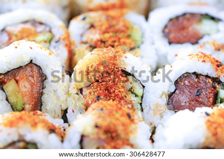 Macro view of a group of tuna and salmon sushi rolls, shallow DOF - stock photo
