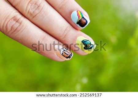Macro view of a woman's fingers against green lush background. Her fingernails are adorned with St. Patrick's day themed nail polish art - glass of beer, Irish hat, pot of gold. - stock photo