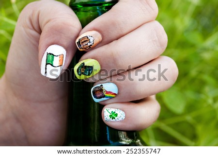 Macro view of a woman's hand holding a beer bottle against green lush background. Her fingernails are adorned with St. Patrick's day themed nail polish art. - stock photo