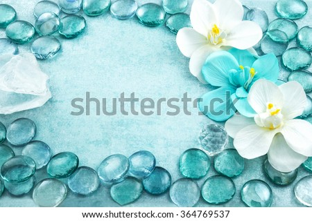 Macro view of blue glass drops with white flowers orchid and bar of sea salt, aqua background - stock photo