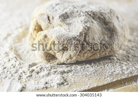 Macro view of bread dough and white flour on rustic wooden cutting board, shallow DOF - stock photo