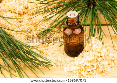 Macro view of glass bottle of oil, wooden sawdust, green pine branches and logs - stock photo