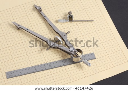 Macro view of mechanical drafting compass and decimal steel scale on yellow grid paper on black background - stock photo