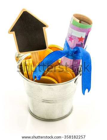 Macro view of metal bucket with gold coins, euro money and wooden house isolated on white background - stock photo