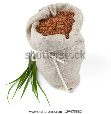 Macro view of sack of red rice with greens isolated on white background - stock photo