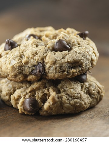Macro view of two chocolate chip cookies stacked on a wooden table, shallow DOF - stock photo