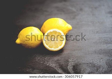 Macro view of vibrant, yellow lemon slice and two whole lemons on dark brown, rustic, wooden table, shallow DOF - stock photo