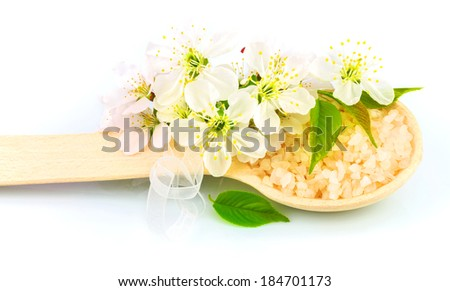 Macro view of wooden spoon with bath salt and white blossom isolated on white background - stock photo