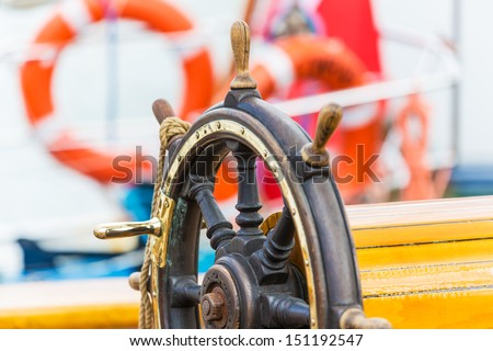 Macro view of wooden steering wheel on sailing ship - stock photo