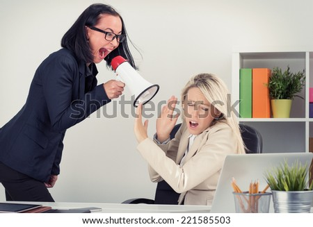 Mad boss shouting at employee on megaphone - stock photo