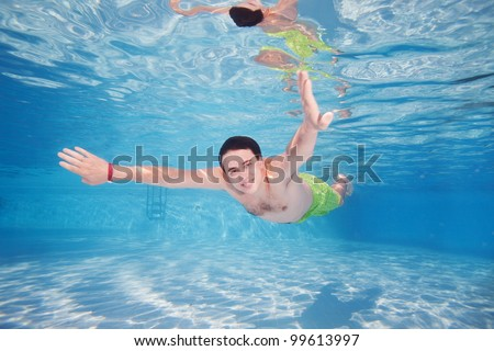 Mad diving in pool - underwater shoot - stock photo