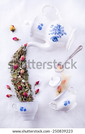 Mad Hatter tea party from Alice in Wonderland, magic porcelain sugar bowl, teapot, cup and tea from dry herbs and roses - stock photo