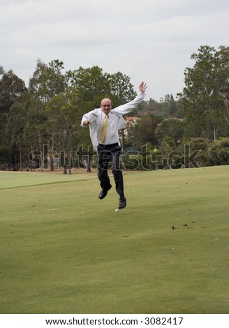 Mad keen Doctor golfer on the golf course showing his elation at the prospect of a hole in one with a putter held above his head and the hole in front of him. - stock photo