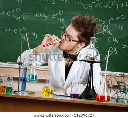 Mad professor sniffs the red liquid in the vial - stock photo