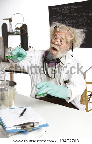 Mad scientist conducts chemistry experiment in his lab - stock photo