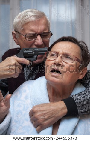 Mad senior couple fighting with a gun. - stock photo