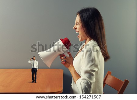 mad woman screaming at man with gun - stock photo