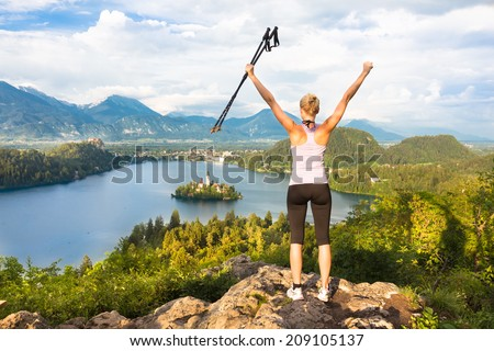 Made it! Young spoty active lady with hiking sticks and hands rised admiring beautiful nature around Bled Lake in Julian Alps, Slovenia.  - stock photo