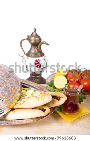 Made with cheese and seasoned ground beef Turkish pide garnished with lemon parsley and tomatoes on the vine. Served with tea and in copper plate. - stock photo