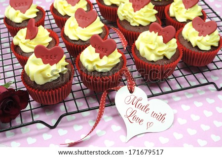 Made with Love, red velvet cupcakes with vanilla frosting and cute red hearts with love messages for Valentines Day, Mothers Day, birthday Christmas or special romantic occasion. - stock photo