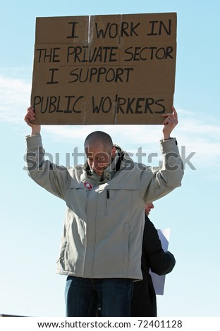 MADISON, WI - FEB 19: Unidentified man protests WI Budget Repair Bill on February 19, 2011 on the capitol square in Madison, WI.  The man holds a sign in support of public workers. - stock photo