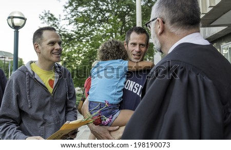 MADISON, WISCONSIN USA - JUNE 6: A gay couple getting married on the steps of the City County Building after a judge struck down Wisconsin's gay marriage ban on Friday June 6, 2014 in Madison, WI - stock photo