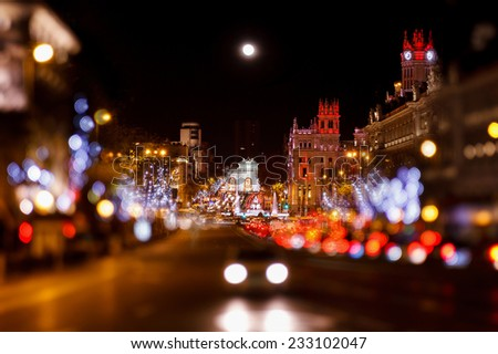 Madrid at Christmas. Rays of traffic lights on Cibeles square, Cibeles fountain in front of the The City Hall or the former Palace of Communications in Madrid, Spain. - stock photo