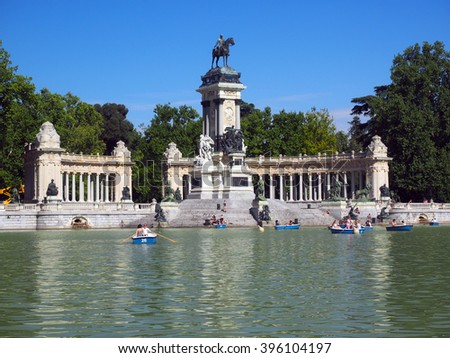 MADRID-MAY 7:  Unidentified people are seen in row boats and relaxing on steps of monument to King Alfonso XII in Retiro Park Madrid Spain on May 7, 2015. - stock photo