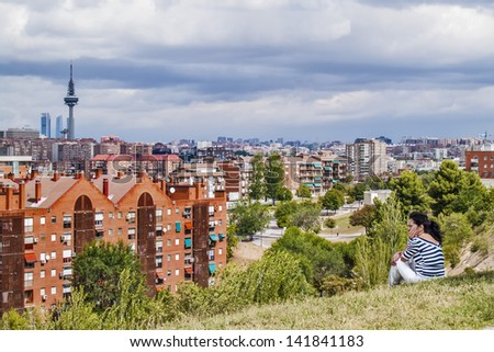 MADRID, SPAIN - AUGUST 15: Skyline with tower Torre Espna on August 15, 2012 in Madrid, Spain. Built in 1982, 232 meters, Emilio Fernandez architect. A woman seated at a park looking. - stock photo