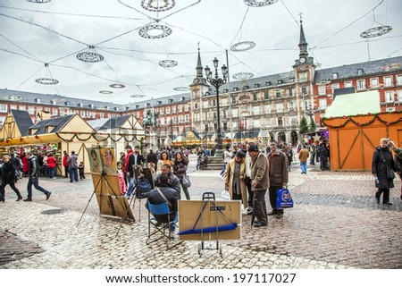MADRID, SPAIN - DECEMBER 20, 2010: People have fun in Christmas time and have a portrait by an artist in the evening at the plaza de Mayor in Madrid in Spain. - stock photo