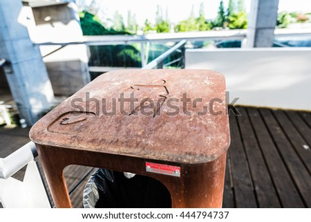 """MADRID, SPAIN - JUNE 19, 2016: a trash can made in rotten metal with the """"drop trash here"""" symbol forged over it, placed at an open public park. - stock photo"""
