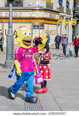 "Madrid, Spain. March 1, 2015. Actors dressed as Hommer Simpson and Minnie Mouse are photographed with tourists by a coins in the ""Puerta del Sol"" in Madrid  - stock photo"