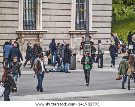 MADRID, SPAIN - MAY 15: Royal Palace surroundings on May 15, 2012 in Madrid, Spain. Diversity of people. Tourist scene. Tourism represents 9% of Spain global income. 53 million tourist in 2010. - stock photo