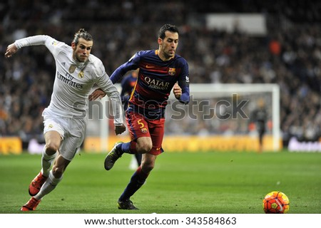 MADRID, SPAIN - November 21st, 2015 :  GARETH BALE of REAL MADRID and BUSQUETS of BARCELONA FC in action looking at the ball during La Liga match  at Santiago Bernabeu Stadium - stock photo