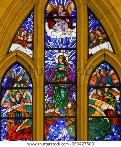 MADRID, SPAIN - NOVEMBER 13, 2015: Stained Glass window depicting Saint John the Evangelist surrounded by angels in the Almudena Cathedral of Madrid, Spain. - stock photo