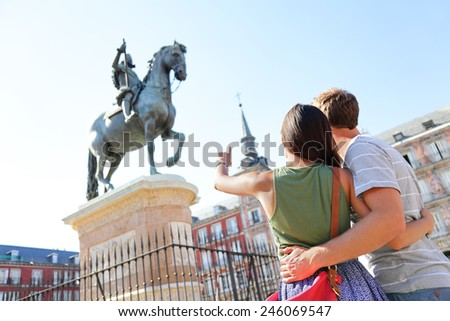 Madrid tourists on Plaza Mayor looking at statue of King Philip III. Travel couple sightseeing visiting tourism landmarks and attractions in Spain. Young woman and man travelling. - stock photo
